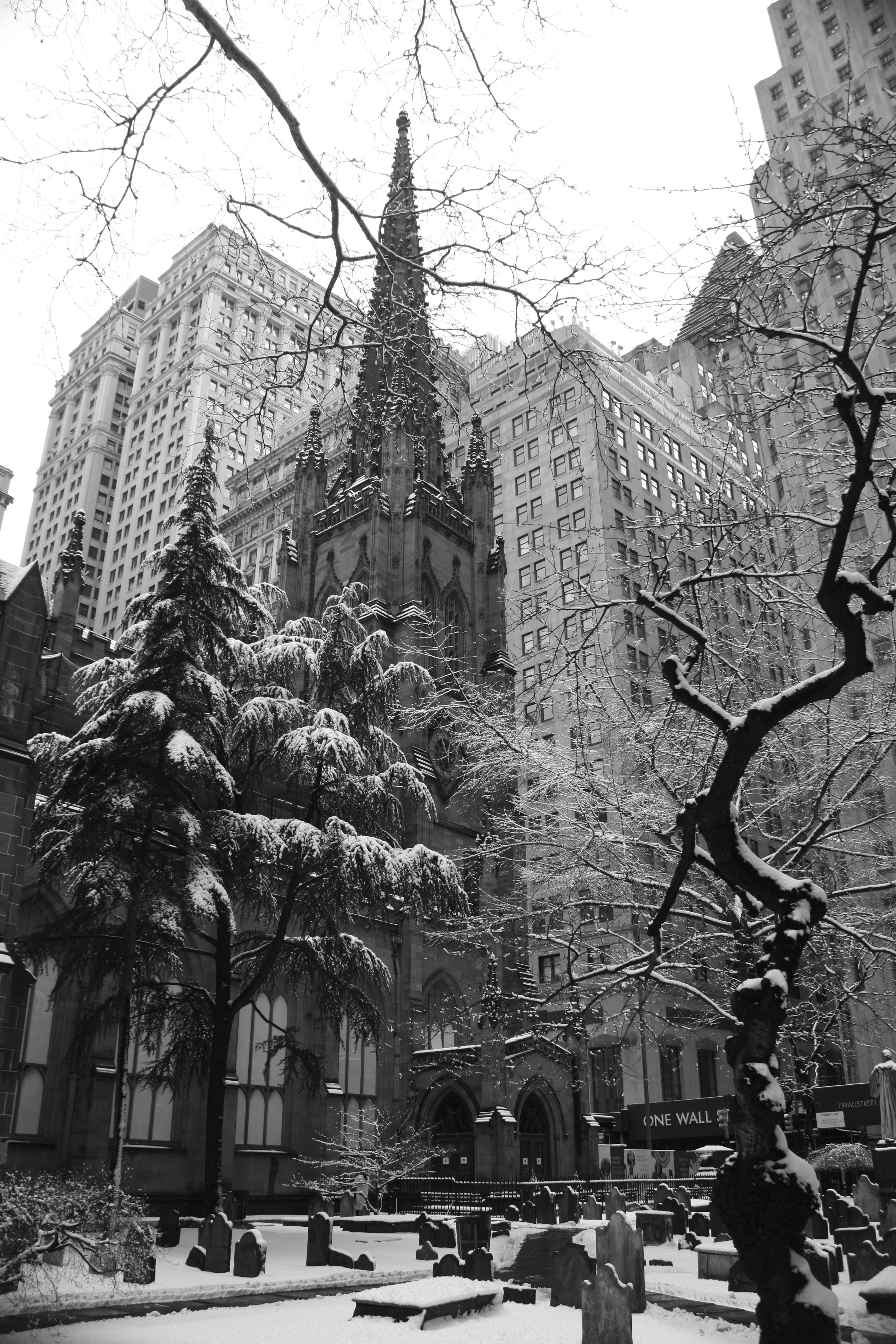 A black and white photo of Trinity Church in New York City. Snow covers the roof and the surrounding tombstones