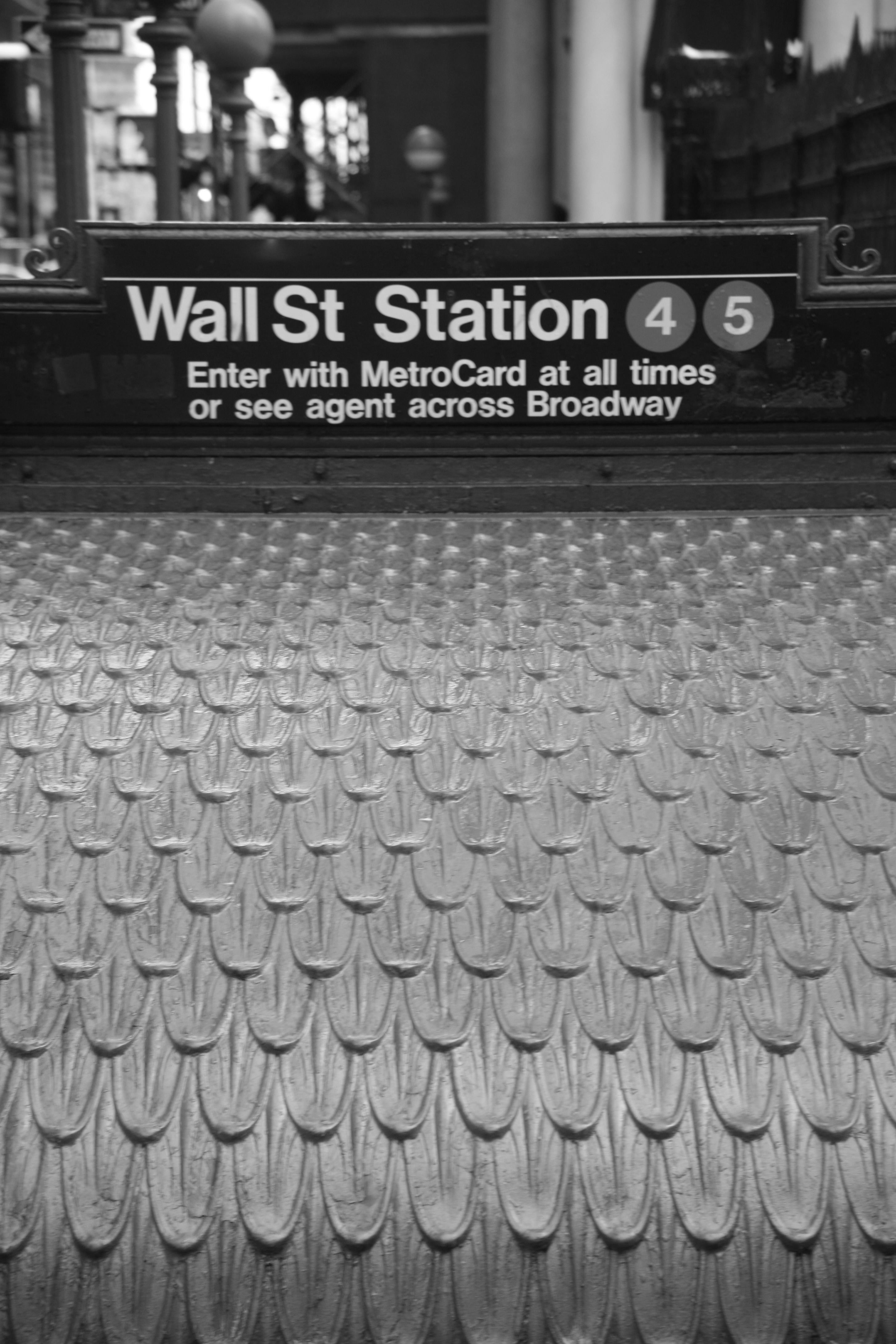A black and white photo of the Wall Street subway station in New York City