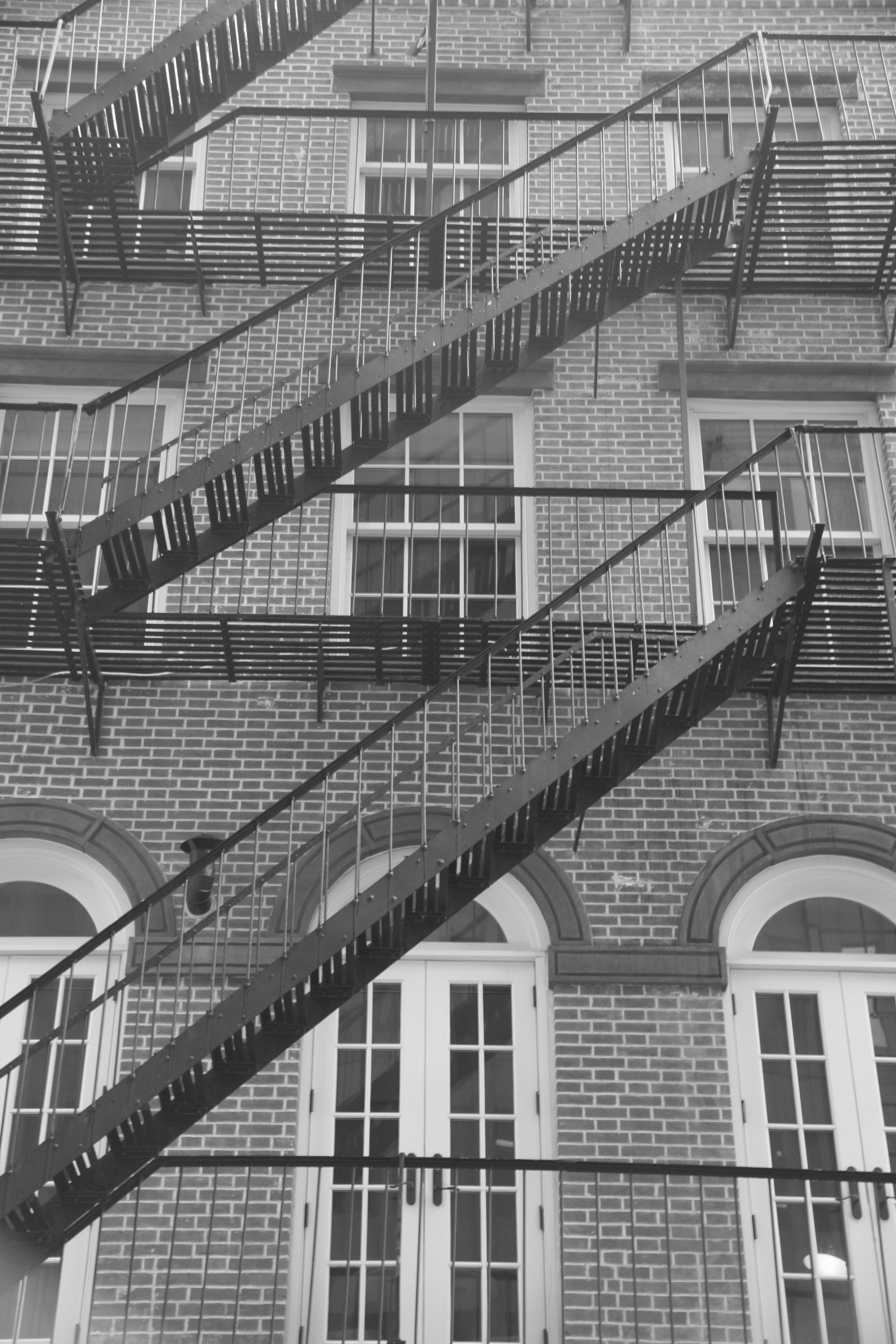 A black and white photo of a tenement building with crisscrossing fire escapes in New York City