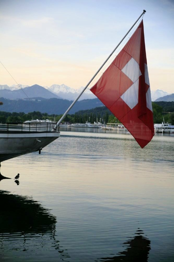 The Swiss flag hanging in the foreground, with a peaceful lake in the background