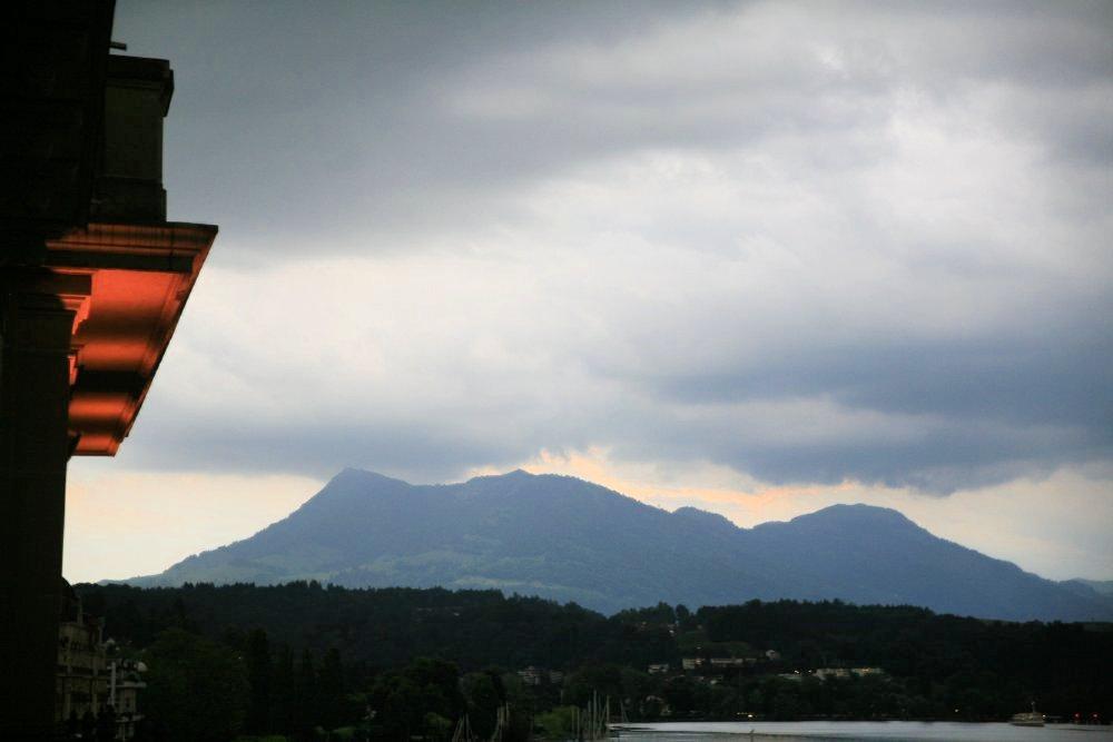 A shadowy mountain beneath an overcast sky at dusk