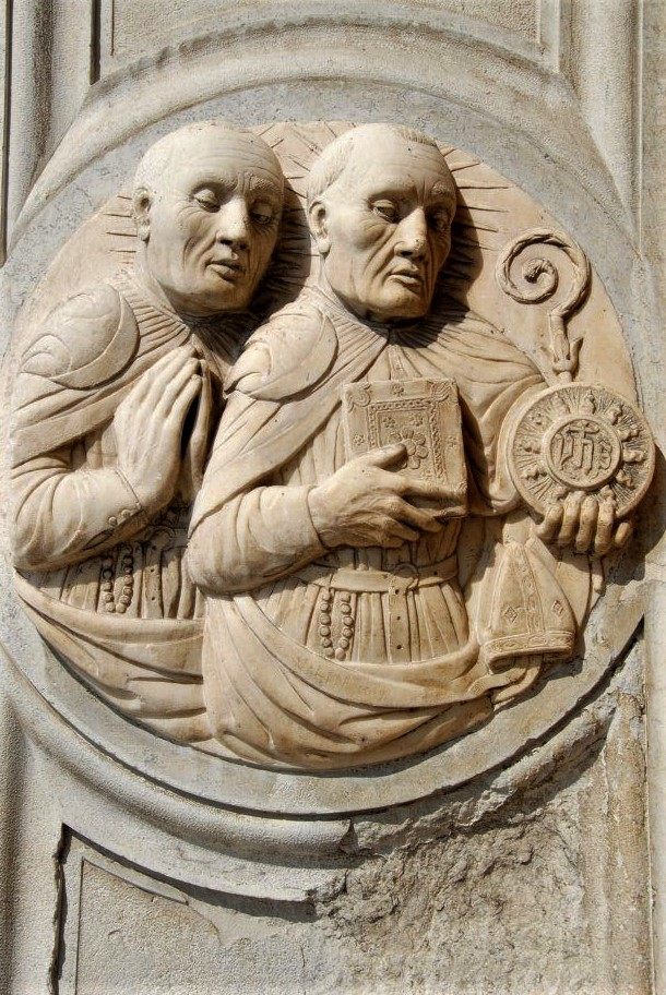 a medieval stone carving depicting two monks holding religious items