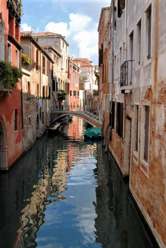 a shadowed, peaceful canal surrounded by orange buildings