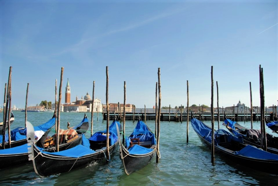 blue gondolas lined up at a dock in the foreground with a view of the water and the city in the background