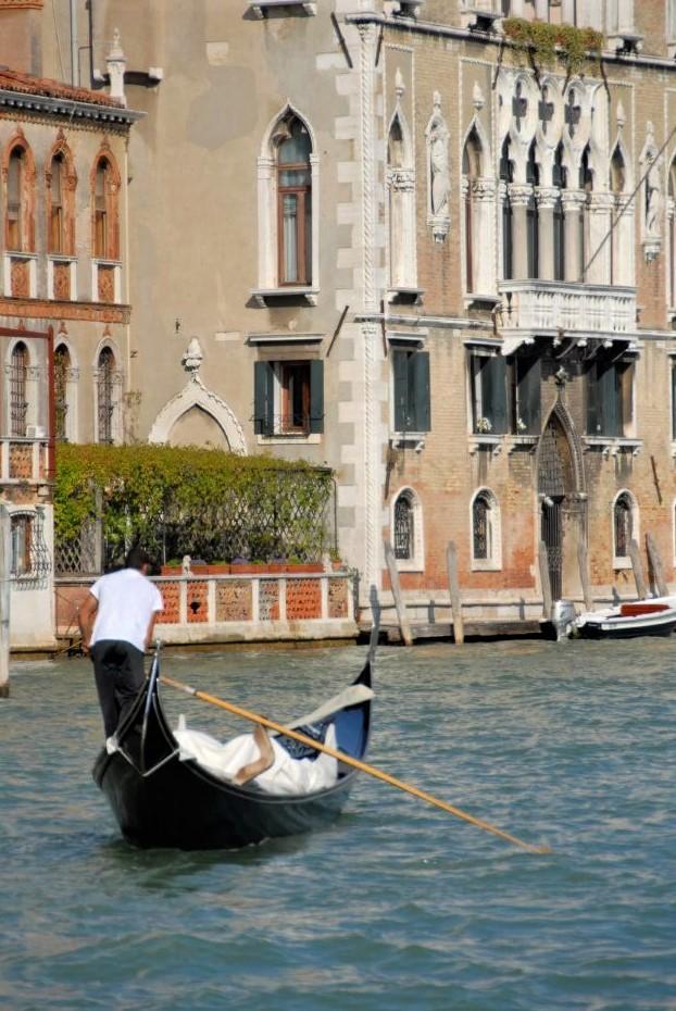 a gondolier steering a gondola on an aquamarine canal