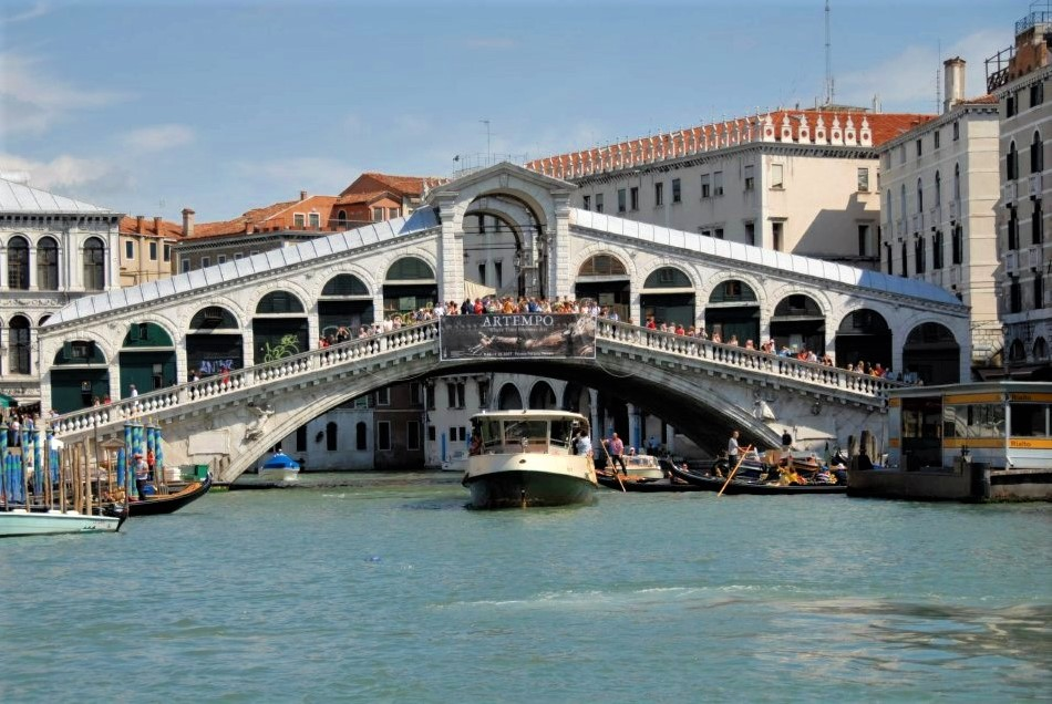 a bridge spanning a canal filled with boats
