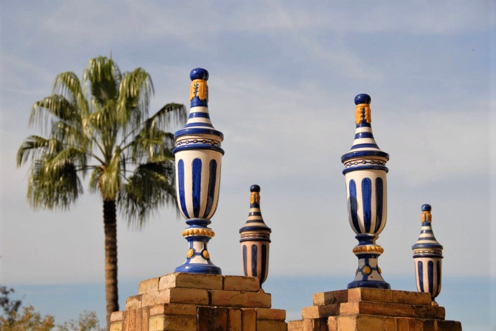 an outdoor scene depicting blue and white sculptures in the shape of vases, perched on pedestals, with a palm tree in the background