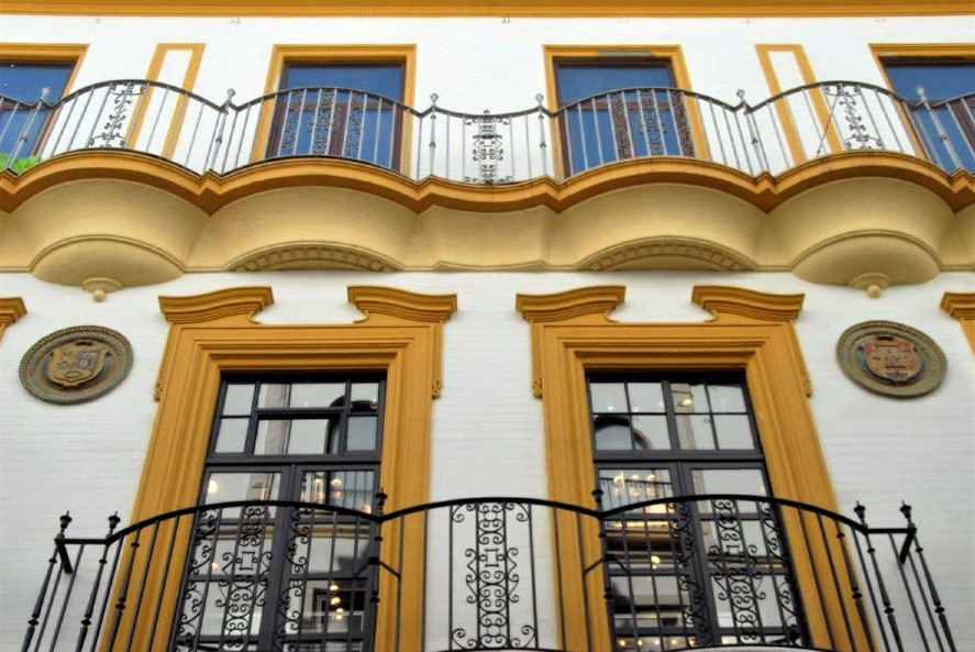 an ornate facade of a white building with mustard-yellow trim and iron balconies