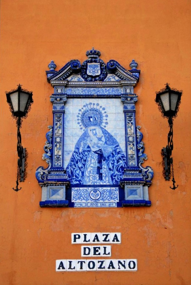 a peach coloured stone wall with a ceramic blue and white plaque, depicting the Virgin Mary, and a sign that reads, Plaza del Altozano
