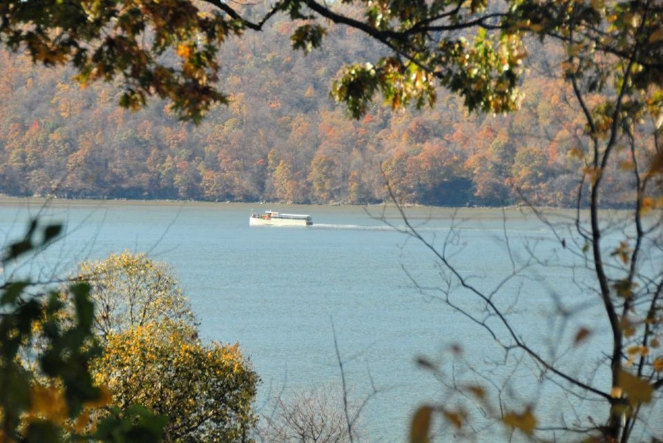 a motor boat skims over a blue lake with orange Autumn foliage on the shores in the foreground and background