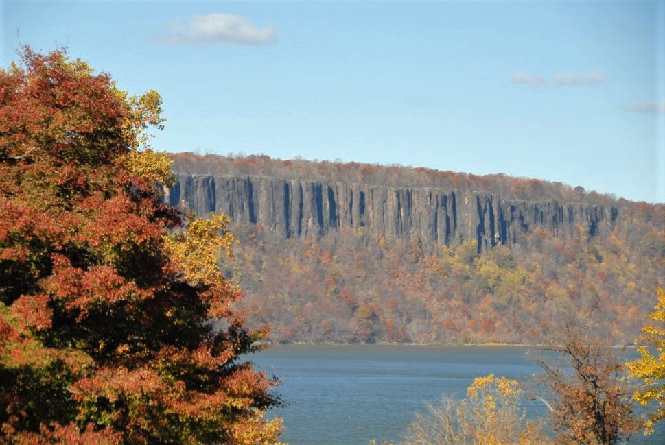 a cliff at the edge of a blue lake, with golden foliage in the foreground