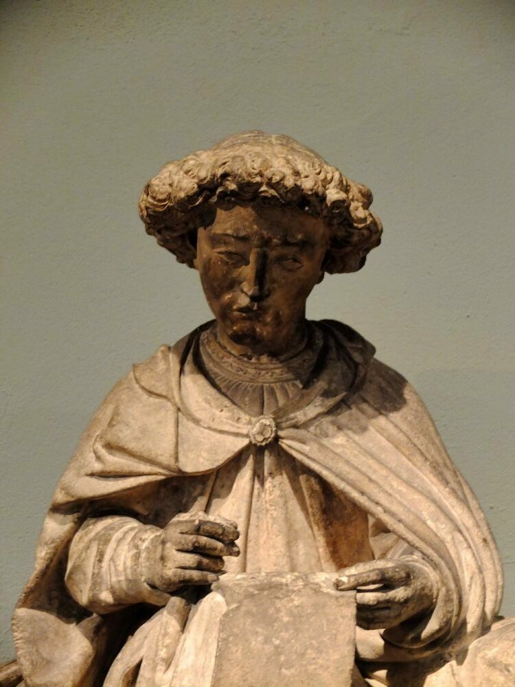 a medieval stone sculpture of a boy with curly hair, wearing a cloak and holding a piece of parchment