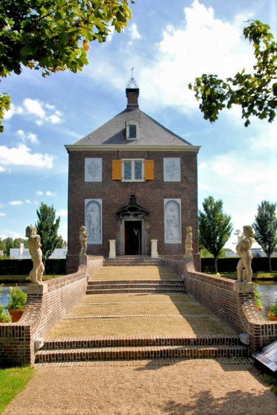 The front walkway bridging the canal and leading to the Hofwijck mansion in the distance. The walkway is lined with four stone statues