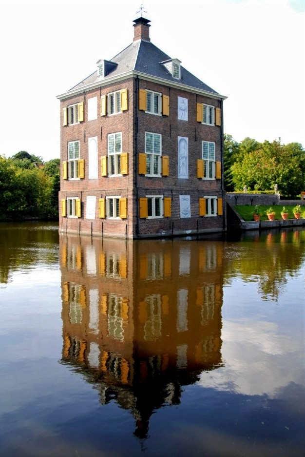 The Hofwijck, a seventeenth-century Dutch mansion made of red brick and adorned with bright orange shutters, sits in the middle of a clear and calm canal