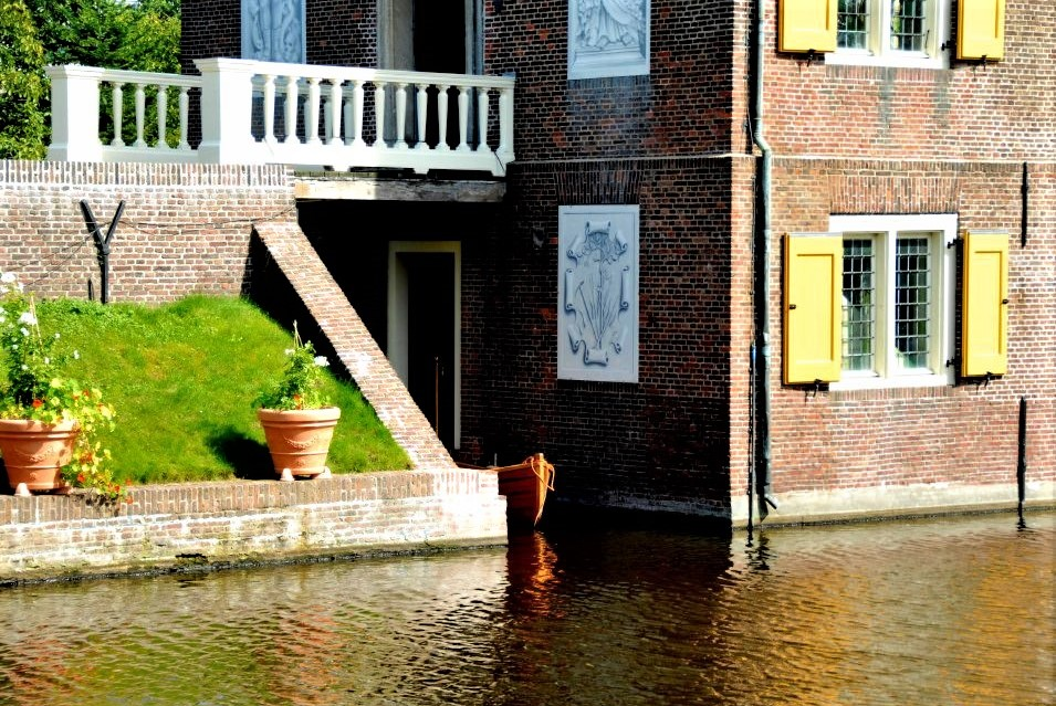 One corner of the Hofwijck mansion where it meets the water of the canal, reflecting in the water. Potted plants sit on a grassy bank nearby