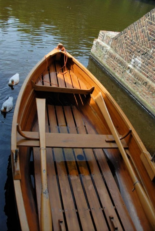 a wooden rowboat sits at a pier in a canal with two white ducks floating in the water around it