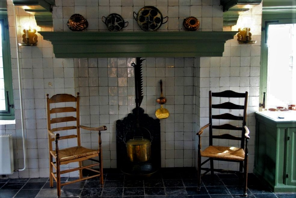two antique wooden rockingchairs sit side by side before a cast-iron stove in a traditional Dutch kitchen