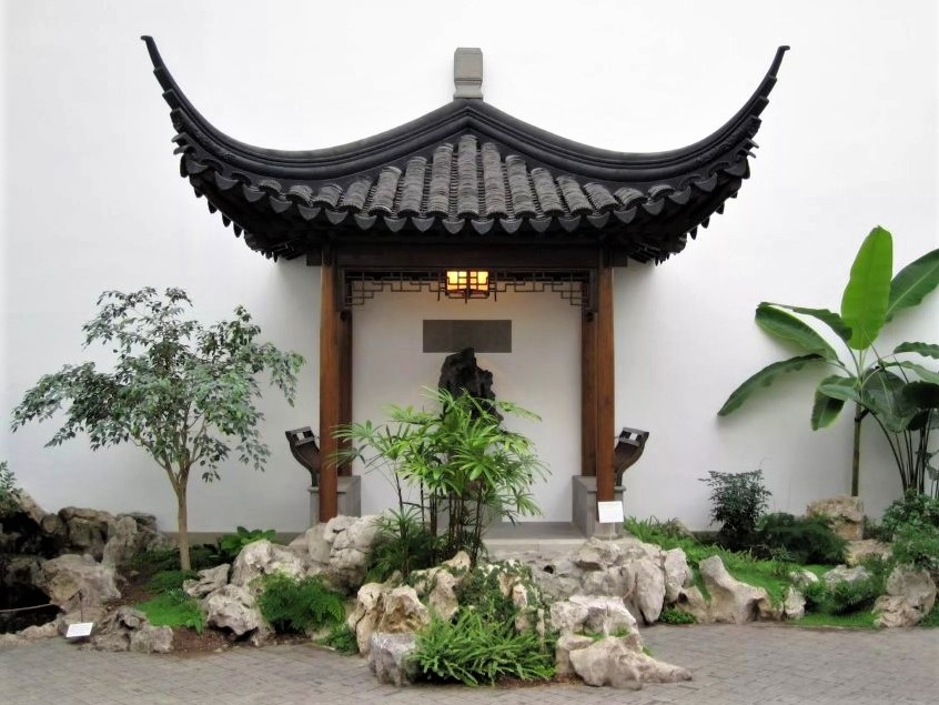 an indoor zen garden with a small pagoda surrounded by green plants and stones