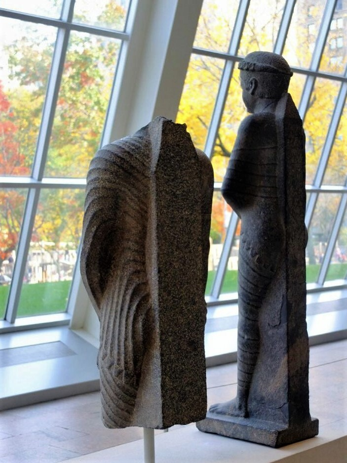 two ancient stone statues facing toward the wall of glass windows