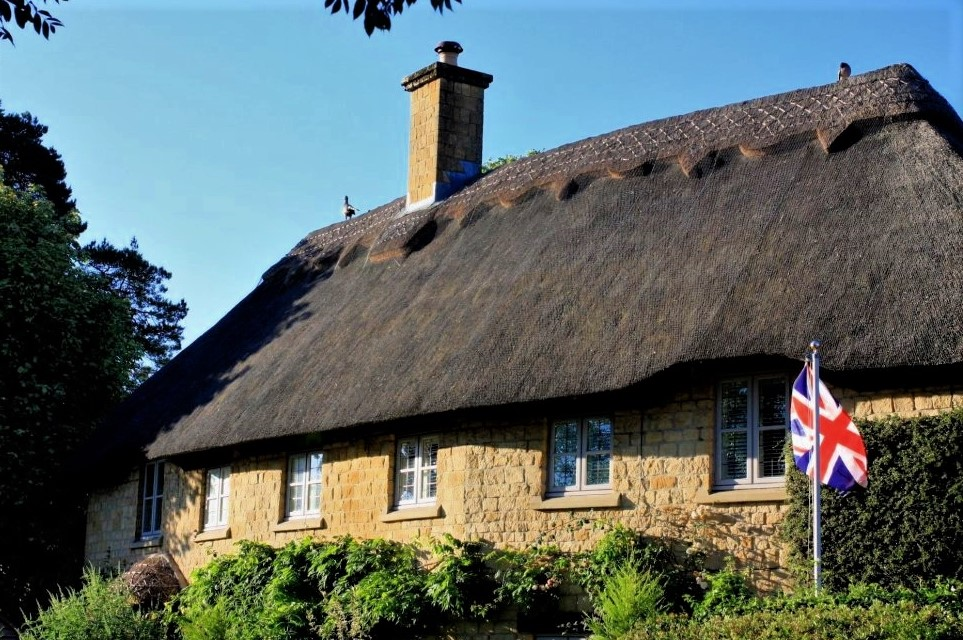 a thatched cottage with a Union Jack flag flying in the front garden