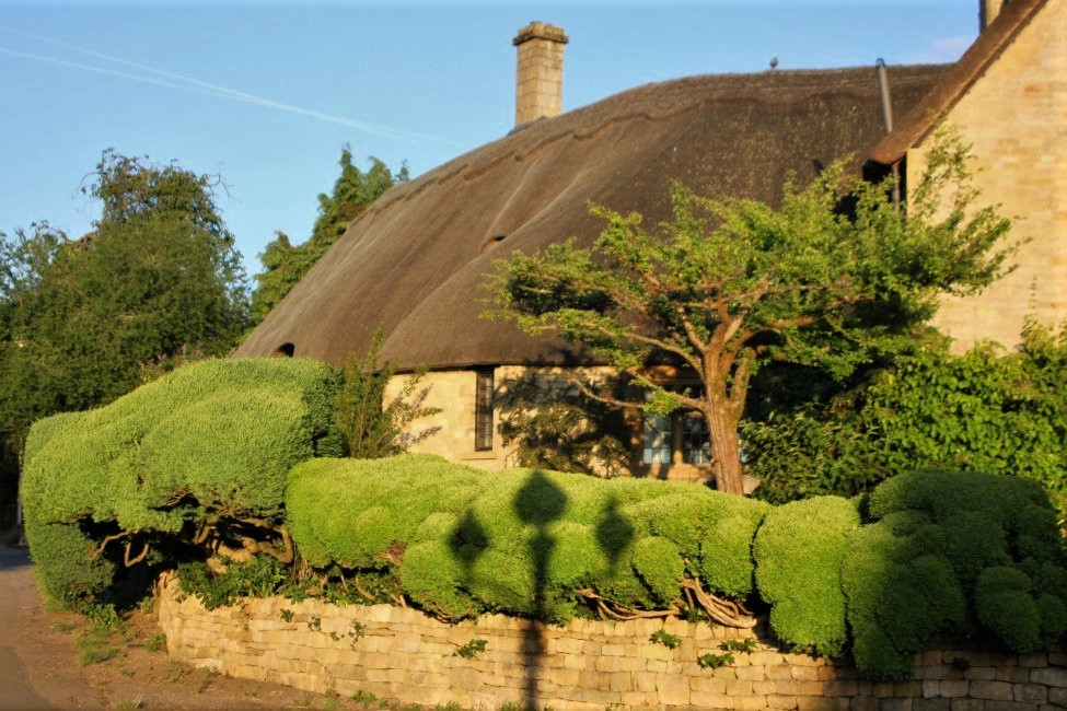 A stone cottage with a sloping thatched roof
