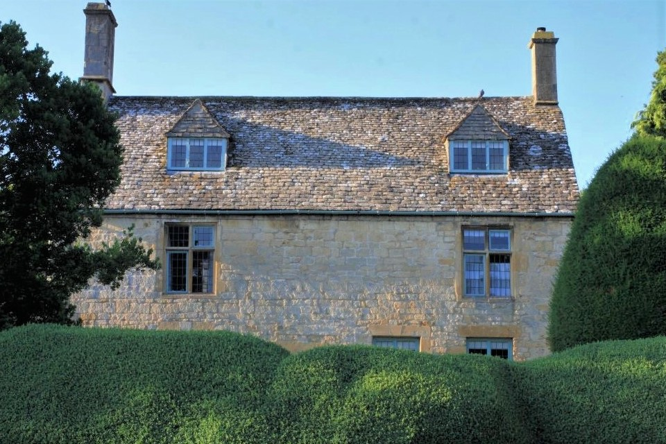 a pale sandstone cottage with two chimneys sits in shadow behind a tall green hedge