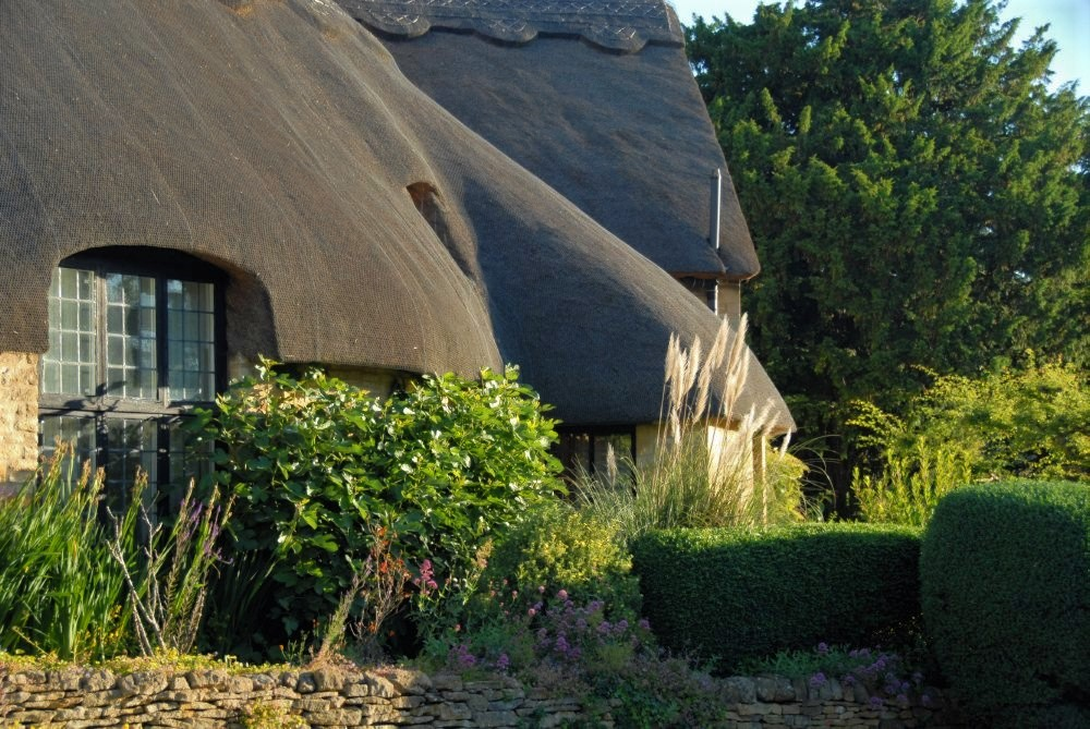 A stone cottage with a sloping thatched roof beside a garden of wildflowers