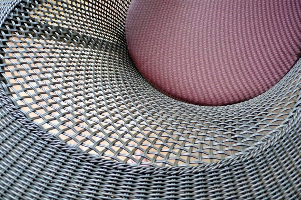 a close-up photo of a wicker chair with a spiraling geometric pattern