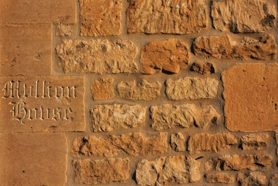 a tan stone wall with a stone plaque embedded, in which is carved the words Mullion House