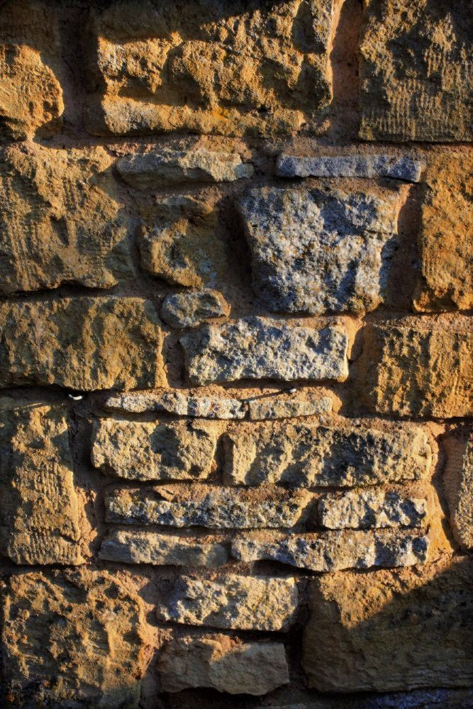 stacks of flat tan stones form a high detailed wall