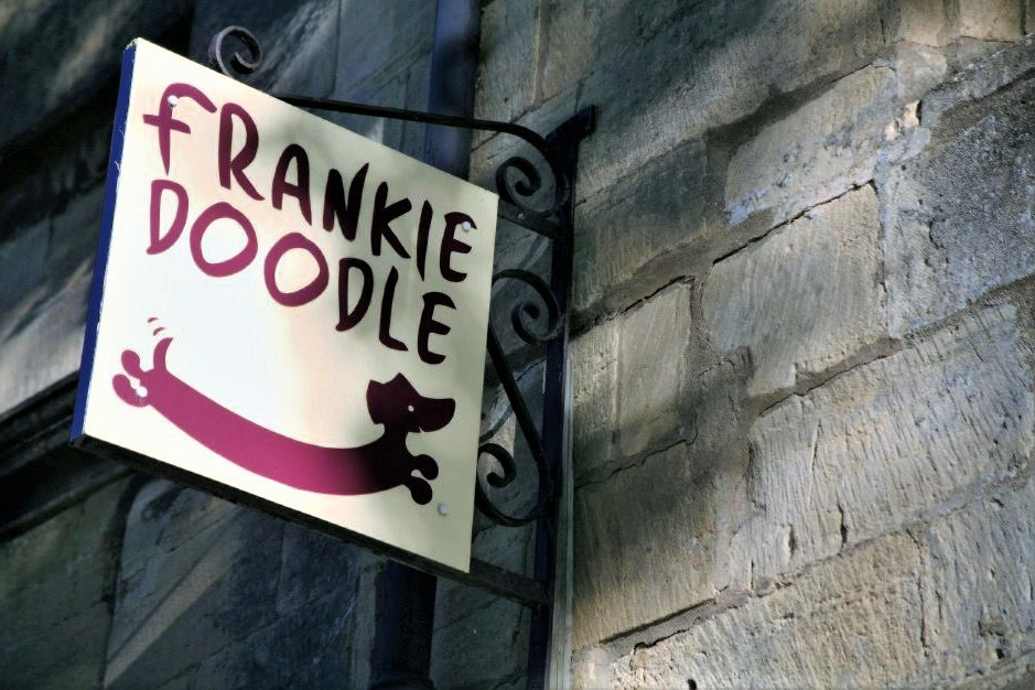 A shop sign hangs from a stone wall. It reads Frankie Doodle and depicts a cartoon weiner dog.