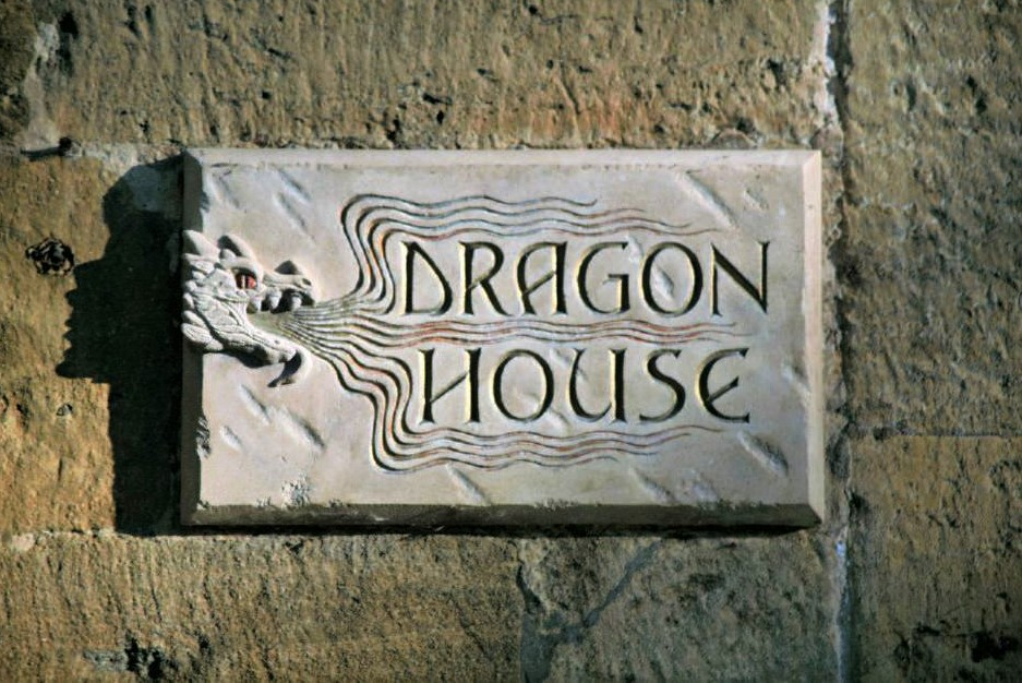 a stone plaque with carved letters reading Dragon House. A carved illustration of a dragon winds around the words.