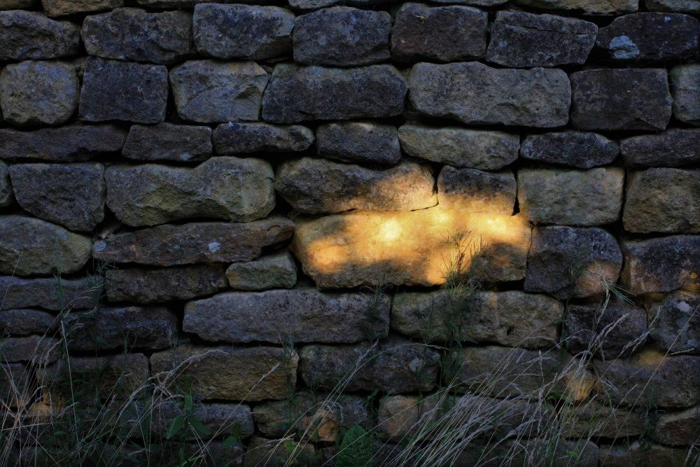 a stone wall cast in deep shadow, illuminated at the center by one small golden sun spot