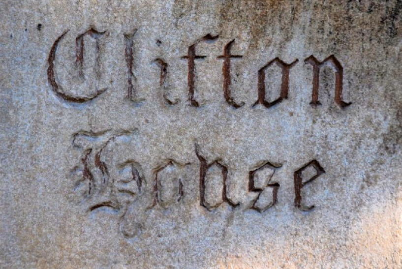 a close-up photo of a stone with carved letters that read Clifton House