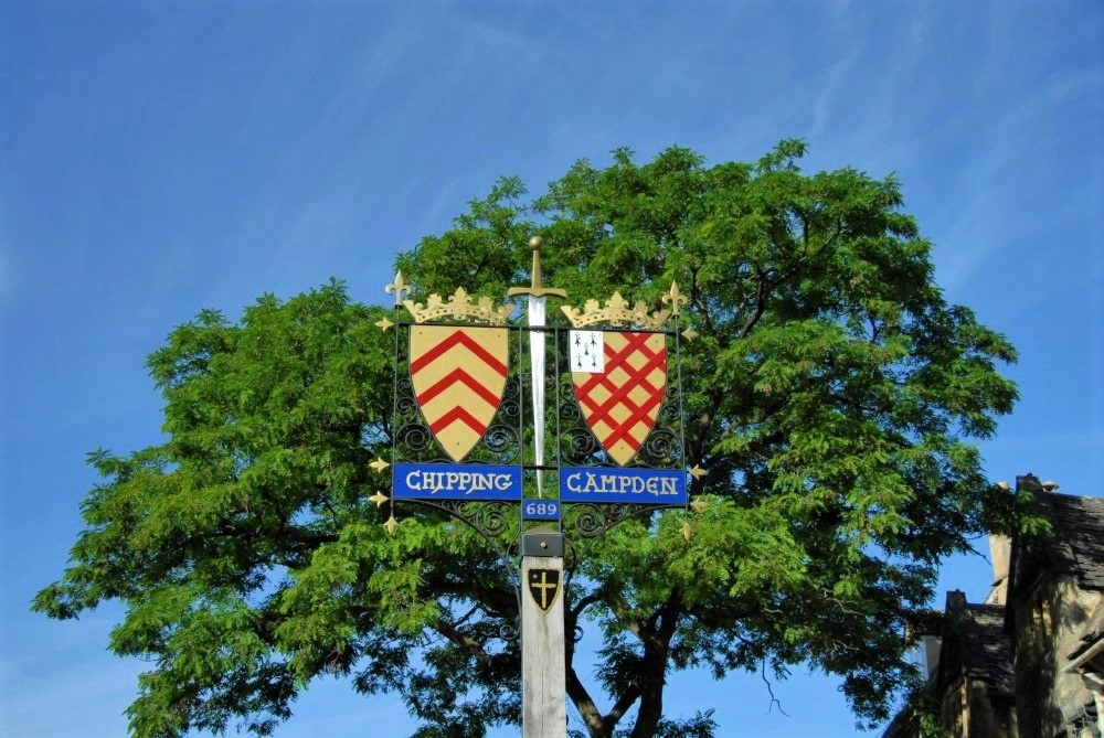 A sign at the top of a pole that features two yellow shields, each with red stripes, and painted with the words Chipping Campden