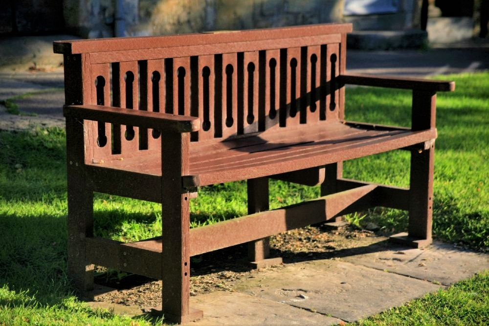 A wooden bench painted maroon, with shafts of sunlight falling upon it