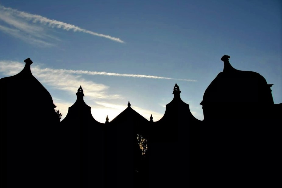The dark silhouettes of buildings with pointed rooves, at dusk