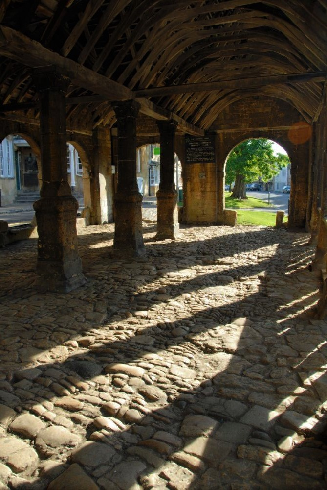 A covered passageway with a cobblestoned path leading to a sunny archway