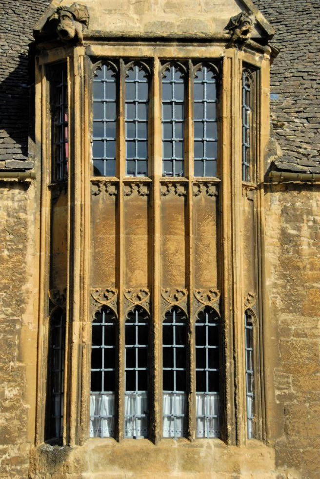 A close-up photo of a Medieval sandstone building with tall, intricately designed windows