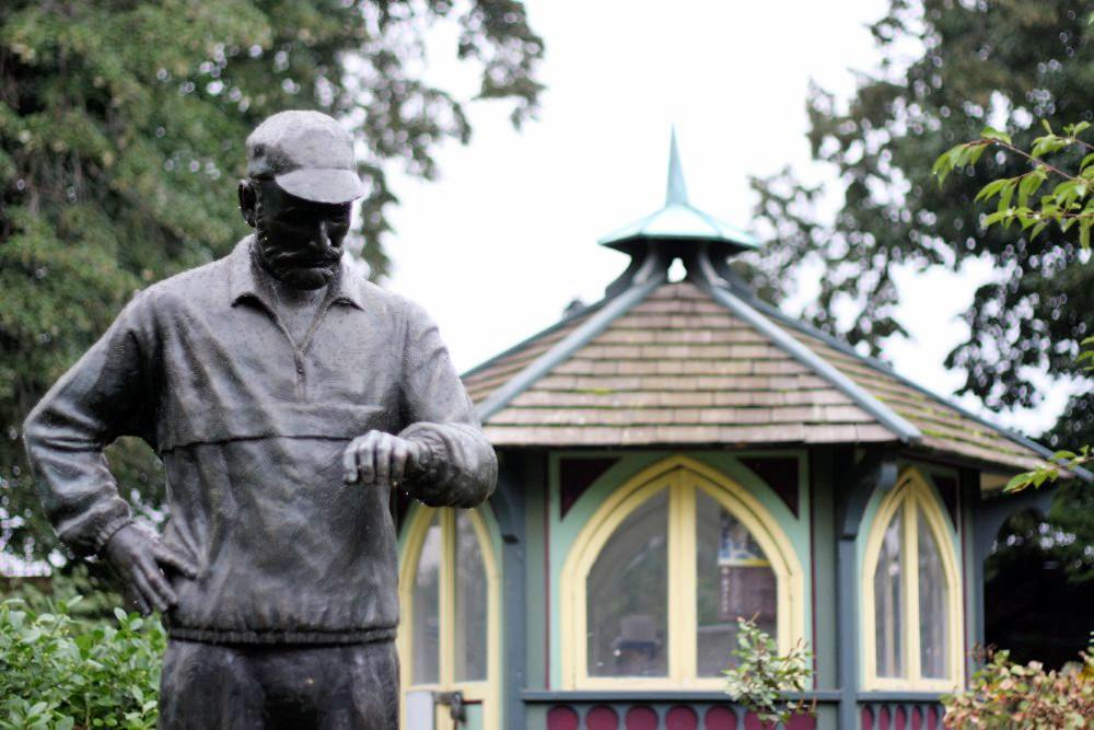 A metal statue of a man checking his watch in the foreground, with an octagonal building among trees in the background