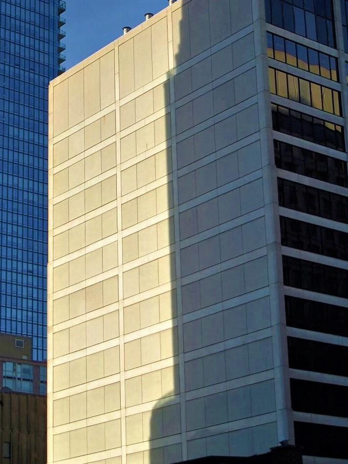 A skyscraper illuminated in afternooon sunlight