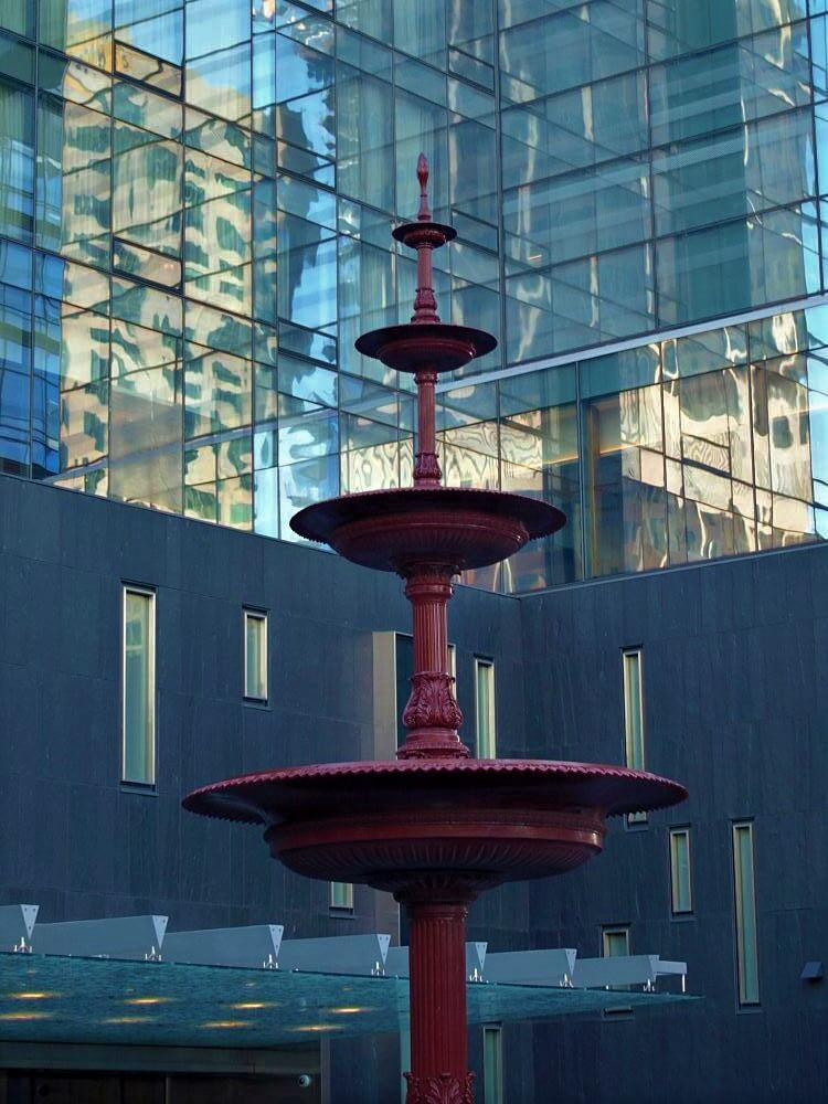 A shadowed fountain surrounded by gleaming skyscrapers