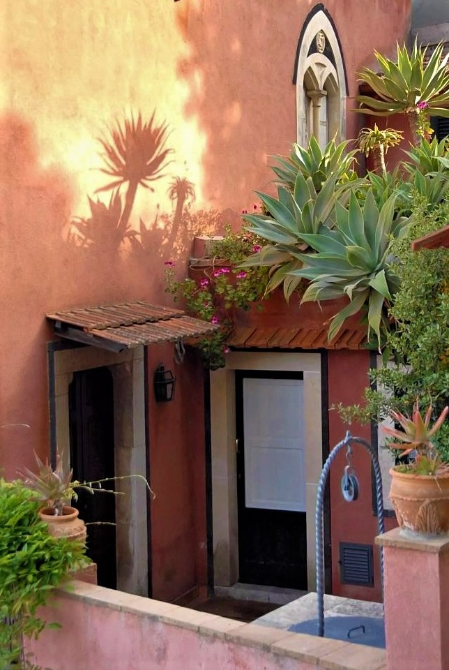 A patio beside a terracotta villa with palm trees and other lush plants. The sun shines on a palm tree in the foreground, splashing its silhouette onto the wall behind it