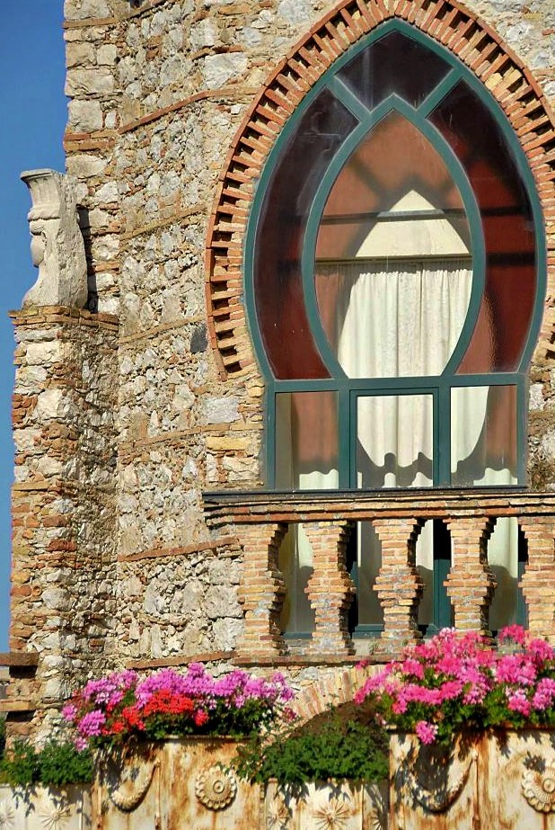 A stone house with a large ornate window in the shape of a pointed oval. Pink flowers sit in pots at the base of the house