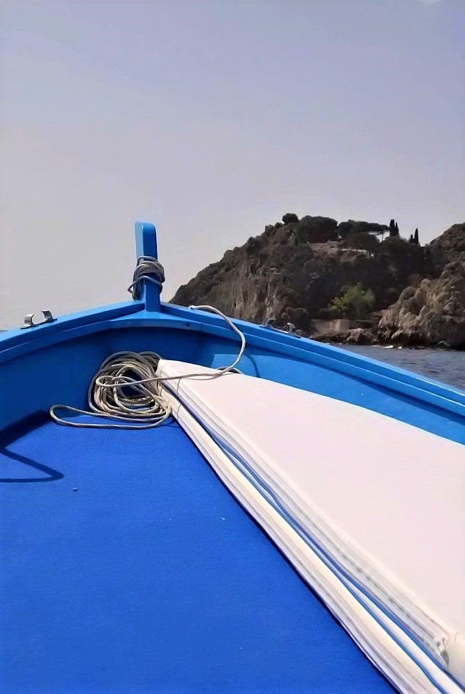 A vibrant blue kayak floating on the water. Large stones rise in the distance along the shore