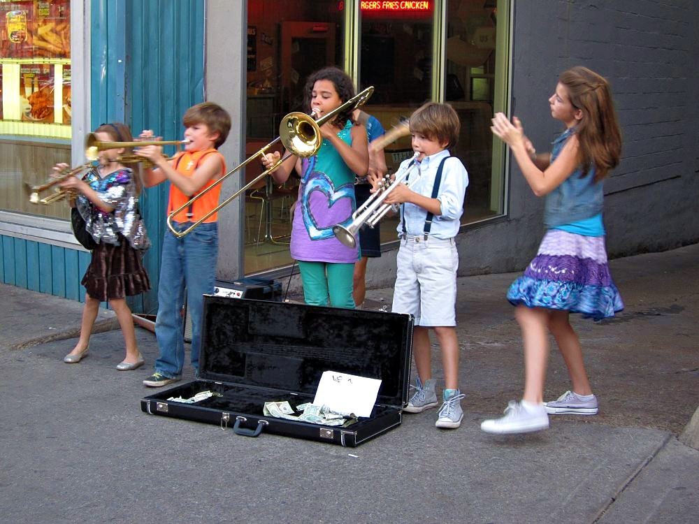 A group of children playing trumpets and trombones