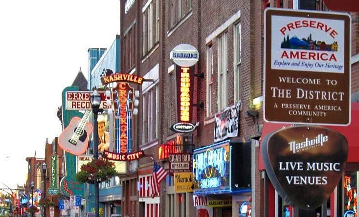 A street in Nashville lined with music halls with colourful neon signs