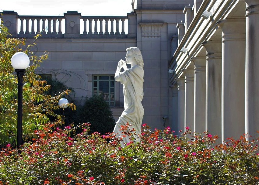 A marble statue of a woman in a flowing gown. The statue stands in a garden amid bushes, beside a Greek-style building