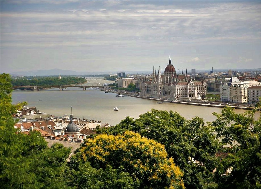 A hilltop view of the city of Budapest, where Budapest Cathedral and the Danube River are visible