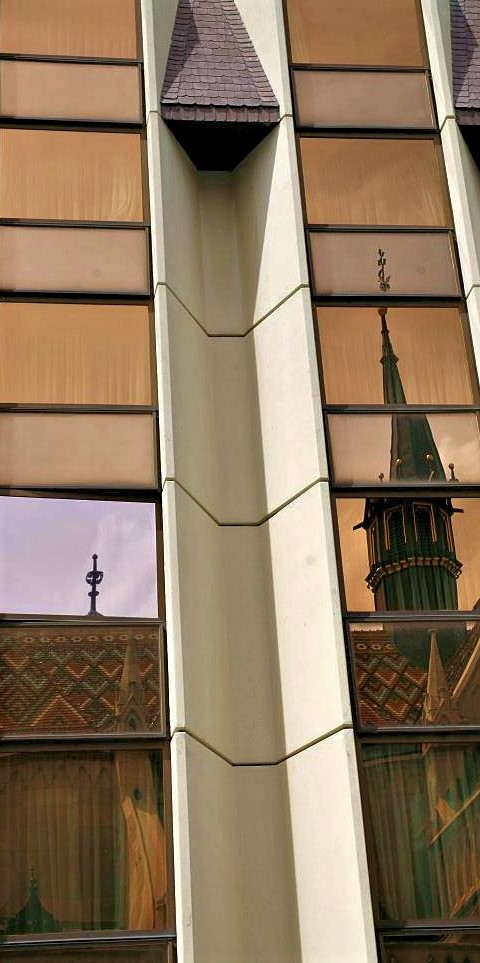 The metal and glass facade of a modern building, with the spire and roof of Budapest Cathedral reflected in the windows